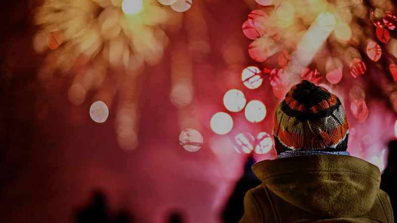 A group of people, seen from behind, watch fireworks. One person in the foreground is in focus, and warmly dressed in overcoat and beanie hat.